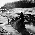 man on snowmobile crossing frozen fields in rural Forget canada by Joe Fox