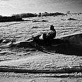 man on snowmobile crossing frozen fields in rural Forget Saskatchewan Canada by Joe Fox