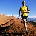 Man Running In Moab, Utah by Scott Markewitz