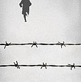 Man Wearing Hat And Coat Running From Barbed Wire Fence In Snow by Lee Avison