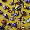 Marbles On Yellow Wooden Table by Garry Gay