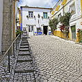Medieval Cobblestone Street In The Fortified Walled European Village Of Obidos by David Letts