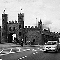 modern traffic driving past Entrance to Macroom Castle County Cork Ireland by Joe Fox