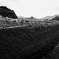 mound of Turf peat cut next to the cut seam in a peat bog in Connemara by Joe Fox