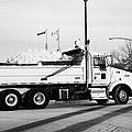 municipal city dump truck taking away snow cleared from parking lots and roads in Saskatoon Saskatch by Joe Fox