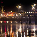 Night On Santa Monica Beach Pier With Bright Colorful Lights Reflecting On The Ocean And Sand Fine A by Jerry Cowart