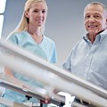 Nurse With Senior Man Using Parallel Walking Bars by Science Photo Library