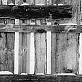 old patched up wooden fence using old bits of wood in snow Forget by Joe Fox
