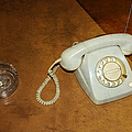 Old Telephone And Ashtray On Brown Table by Matthias Hauser