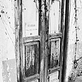 old weathered brown wooden door entrance to abandoned house with cracked stucco walls and for sale sign in spanish in Tacoronte Tenerife Canary Islands Spain by Joe Fox