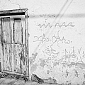old weathered green painted wooden door entrance to abandoned house with cracked stucco walls and graffitti in Tacoronte Tenerife Canary Islands Spain by Joe Fox