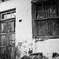 old weathered wooden door entrance to abandoned house 18 with window and cracked stucco walls in Los Banquitos Tenerife Canary Islands Spain by Joe Fox