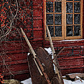 Old wheelbarrow leaning against barn in winter by Sandra Cunningham