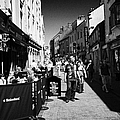 pedestrians and drinkers enjoying a sunday afternoon drink in the bunch of grapes pub high street Ga by Joe Fox