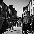 pedestrians walking down closed pedestrian area of quay street on sunny sunday afternoon Galway city by Joe Fox