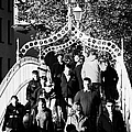 People Crossing The Hapenny Ha Penny Bridge Over The River Liffey In Dublin At A Busy Time by Joe Fox