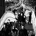 People Crossing The Hapenny Ha Penny Bridge Over The River Liffey In Dublin At A Busy Time Vertical by Joe Fox