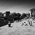 people enjoying the sunshine on the quay next to the corrib river on a sunday afternoon Galway city  by Joe Fox