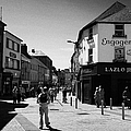 people walking down pedestrian area william street on a sunday Galway city county Galway Republic of by Joe Fox