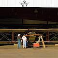 Pilot Works On Antique Plane In Hood by Richard Hallman