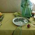 Plates, Apples And A Vase On A Green Tablecloth by Horst P. Horst