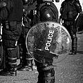 Psni Officer In Full Riot Gear With Shield On Crumlin Road At Ardoyne Shops Belfast 12th July by Joe Fox