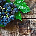 Purple Grapes On A Rustic Wooden Table by Ken Biggs