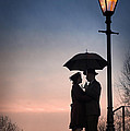 Romantic Couple Under A Street Lamp At Sunset by Lee Avison