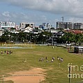 Schoolchildren Practicing On Playing Field With Singapore Skyline In Background by Imran Ahmed