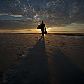 Silhouette Of A Man Wearing Hat And The Bag In Hand Walking On The Seashore by Jaroslaw Blaminsky