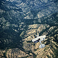 Small Plane Flying Over Mountains by Jill Battaglia