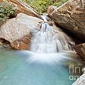 Small Waterfall Casdcading Over Rocks In Blue Pond by Stephan Pietzko