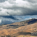 Storm Clouds Floating Above Mountains by Susan Wiedmann