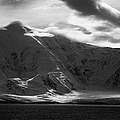 sunlight breaking through clouds on snow covered landscape of anvers island and neumayer channel Ant by Joe Fox