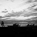 sunset over couple walking along the beach at playa de las americas Tenerife Canary Islands Spain by Joe Fox