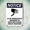 Surveillance Sign On Concrete Wall by Bryan Mullennix