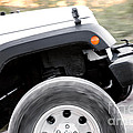 Suv Off Road Vehicle In Action With Spinning Wheel by Gunter Nezhoda