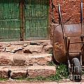 Rusty Wheelbarrow And Green Door by James Brunker
