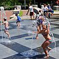 Joyful Young Girl Playing In Fountain by Ginger Wakem