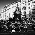 tourists and visitors sit on the steps of the eros statue in picadilly circus London England UK by Joe Fox