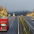 Trucks Driving Through A Misty Mountain Pass by Christian Lagereek