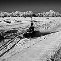 two men on snowmobiles crossing frozen fields in rural Forget Saskatchewan Canada by Joe Fox