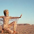 Veruschka Von Lehndorff Posing In A Desert by Franco Rubartelli