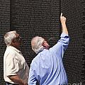 Veterans Look For A Fallen Soldier's Name On The Vietnam War Memorial Wall by B Christopher