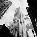 View Of The Empire State Building And Surrounding Buildings And Cloudy Sky West 33rd Street New York by Joe Fox