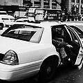 white caucasian passenger closes rear door of yellow cab on taxi rank at crosswalk on 7th Avenue by Joe Fox