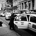 white middle aged passengers exit from yellow cab rear door at taxi rank on 7th Avenue by Joe Fox