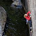 Woman Climbing Above A River by Corey Rich