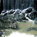 Woman Flyfishing Below Waterfall by Peter Dennen
