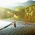 Woman Walking On Log In Alpine  Lake by Thomas Barwick
